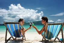 stock-photo-couple-on-a-tropical-beach-in-chaise-lounge-51737842